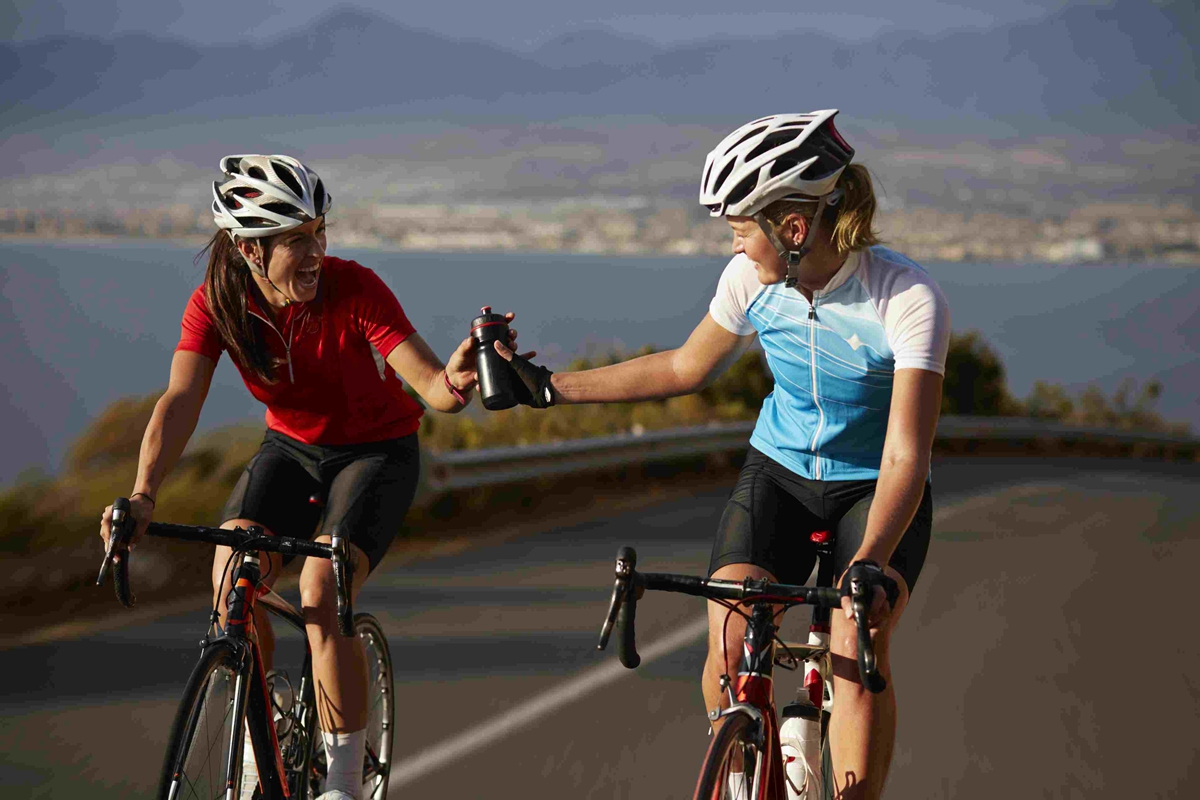 cyclist-passing-water-bottle-to-training-partner-561405173-5a3543daeb4d520037b1c1a4.jpg
